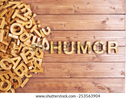 Word humor made with block wooden letters next to a pile of other letters over the wooden board surface composition
