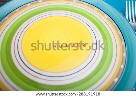 Word Hunger written with pasta on an empty colorful dish - stock photo