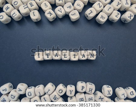 Word Italian of small white cubes next to a bunch of other letters on the surface of the composition on a dark background                                - stock photo