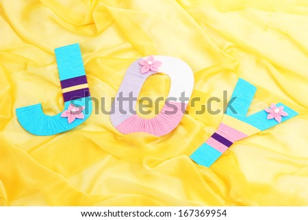 Word Joy created with brightly colored knitting yard on fabric background