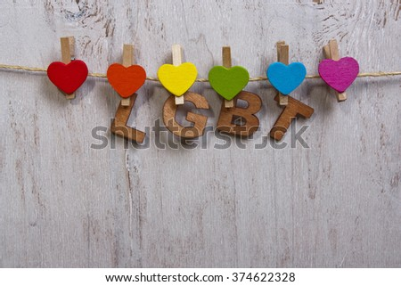 word LGBT rainbow and hearts on a white wooden background.LGBT symbol - stock photo