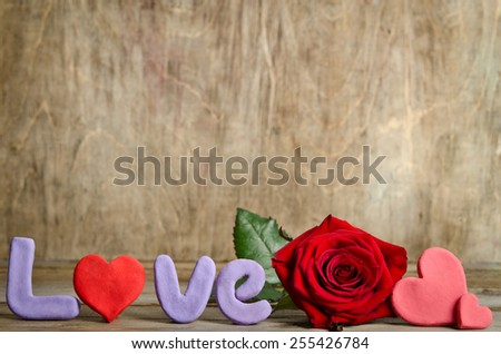 Word Love composition on the wooden board surface and  hearts handmade around rose. Letters and hearts made from salt dough - stock photo