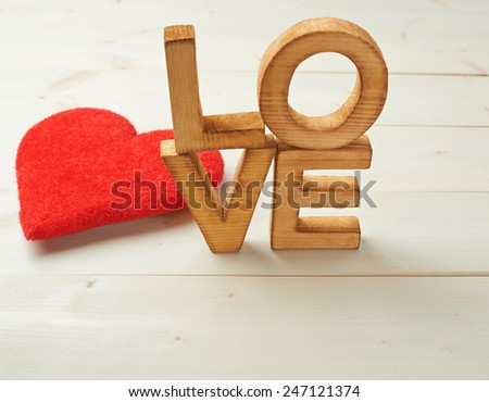Word Love made with block letters over the wooden surface next to a single red heart as a Valentine's Day love composition, background - stock photo
