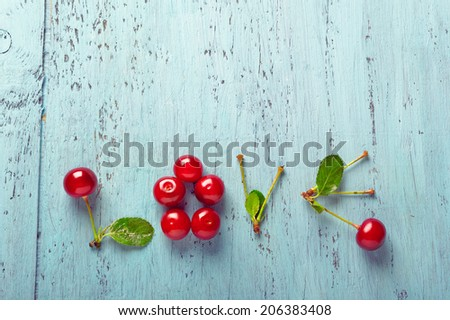 Word Love made with cherries on an old wooden cutting board - stock photo