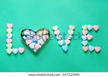 word love made with heart shaped powder sugar candies on green background  - stock photo
