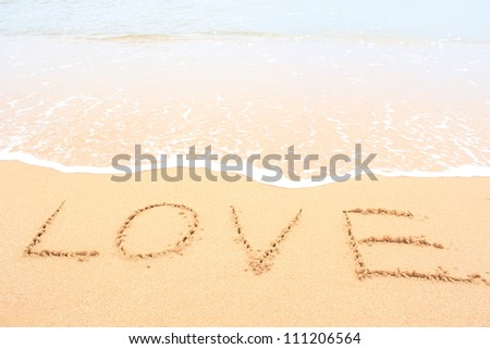 Word LOVE on sand - stock photo