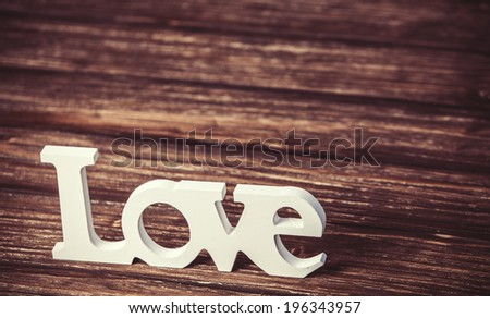 Word love on wooden table.