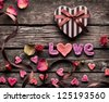 Word Love with Heart shaped Valentines Day gift box on old vintage wooden plates. Sweet holiday background with rose petals, small hearts, curved ribbon. - stock photo