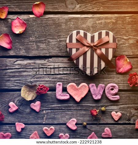 Word Love with heart shaped Valentines Day gift box on old vintage wooden plates. Sweet holiday background with rose petals and dried rose flowers. - stock photo