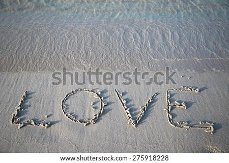 Word love written in sand  - stock photo