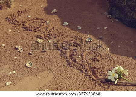 word 'Love' written in the sand on the beach. - stock photo