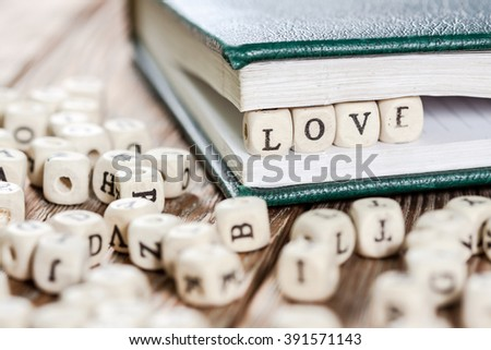 Word LOVE written on a wooden block in a book. On old wooden table.