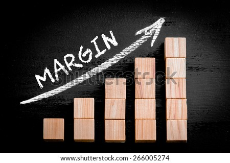 Word Margin on ascending arrow above bar graph of Wooden small cubes isolated on black background. Chalk drawing on blackboard. Business Concept image. - stock photo