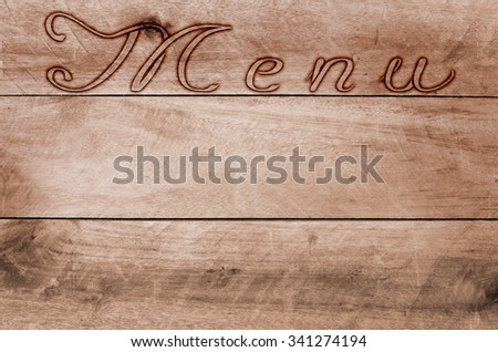 Word menu written, burned lettering on wooden brown background.