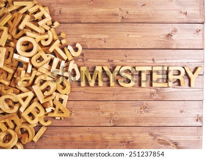 Word mystery made with block wooden letters next to a pile of other letters over the wooden board surface composition - stock photo