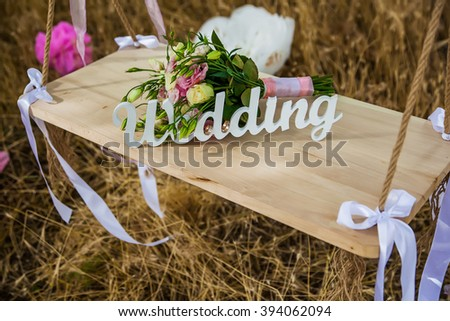 Word of wedding and bridal bouquet on the wooden swing