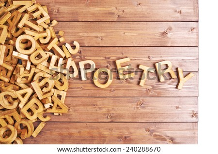 Word poetry made with block wooden letters next to a pile of other letters over the wooden board surface composition - stock photo