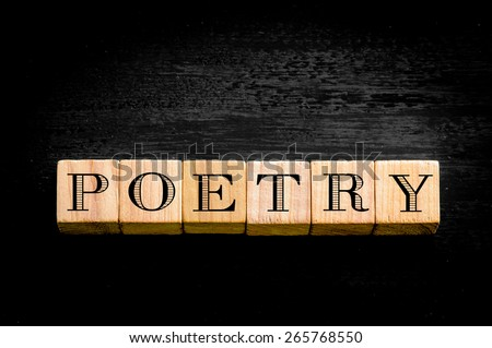 Word Poetry. Wooden small cubes with letters isolated on black background.Concept image.