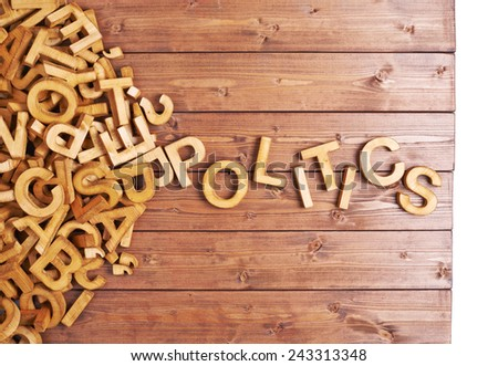 Word politics made with block wooden letters next to a pile of other letters over the wooden board surface composition - stock photo