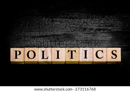 Word POLITICS. Wooden small cubes with letters isolated on black background with copy space available. Concept image.