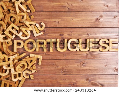 Word portuguese made with block wooden letters next to a pile of other letters over the wooden board surface composition - stock photo