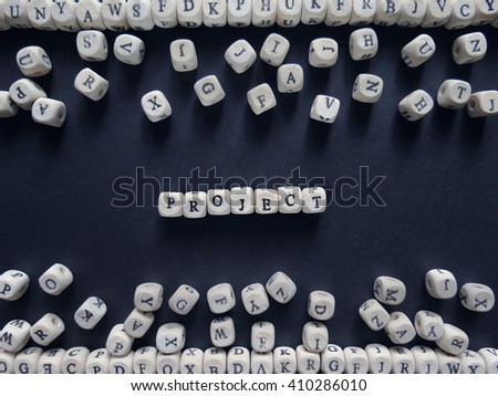 Word Project of small white cubes next to a bunch of other letters on the surface of the composition on a dark background