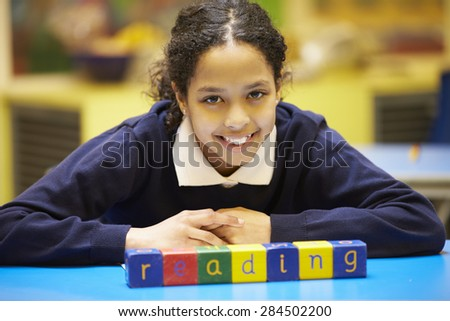 "Word ""Reading"" Spelt In Wooden Blocks With Pupil Behind - stock photo"