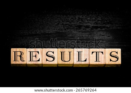 Word Results.Wooden small cubes with letters isolated on black background.Concept image.