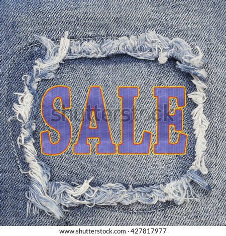 Word SALE on destroyed torn denim blue jeans patch background, close up
