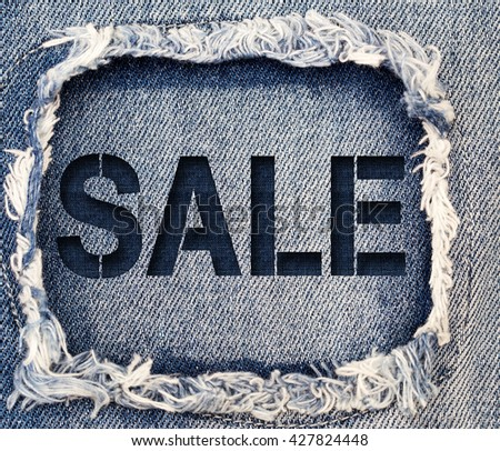 Word SALE on destroyed torn denim blue jeans patch background, close up - stock photo