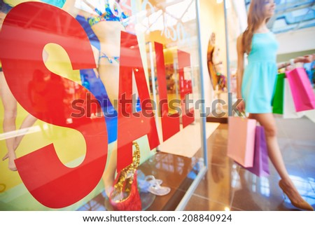 Word �¢??sale�¢?? on shop window with young shopper with paperbags on background - stock photo