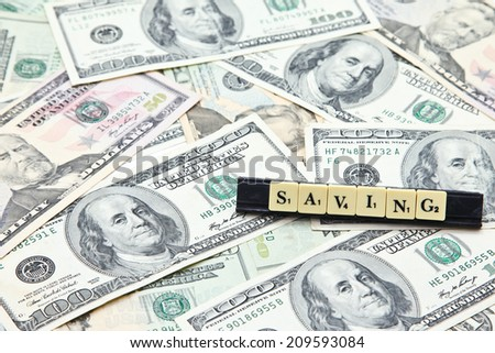 Word saving on pile of US dollar banknotes