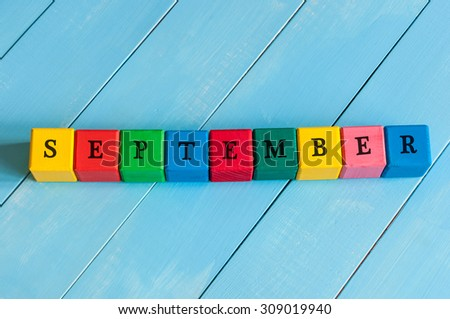 Word September - one of autumn month on colorful wooden cubes with light wood background. - stock photo