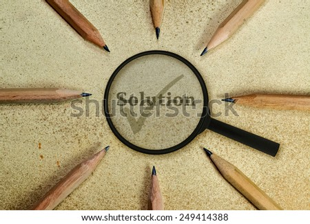 Word Solution under a magnifying glass on vintage background - stock photo