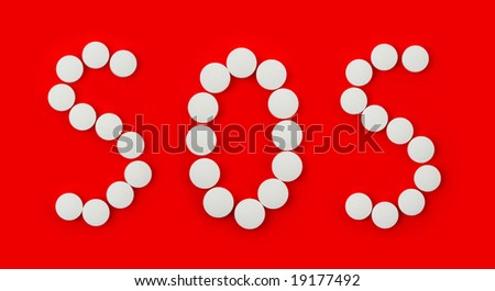 Word SOS made of pills isolated on red background