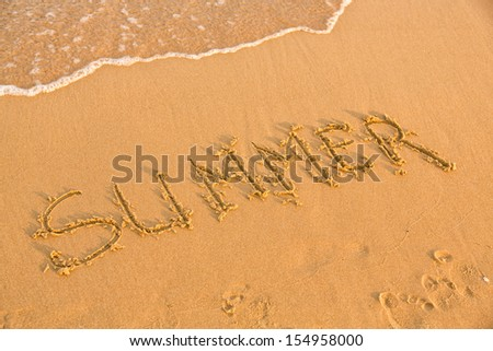 Word summer on the yellow sandy beach, text