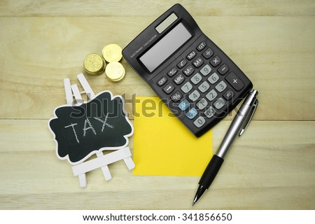 Word tax on blackboard with coins, calculator and pen - stock photo