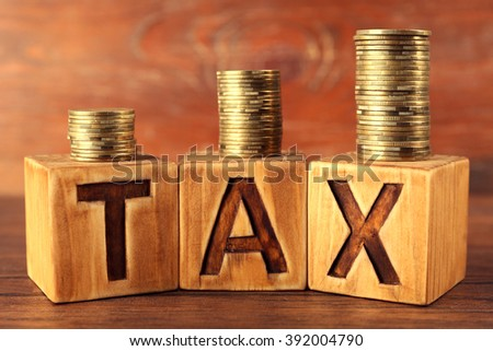 Word tax with stacked coins on wooden background