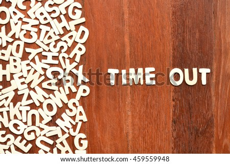 Word time out made with block wooden letters next to a pile of other letters over the wooden board surface composition - stock photo