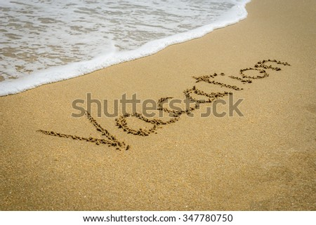 Word vacation on the beach sand - vacation and travel concept