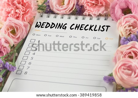word wedding checklist note paper on pink flower background - stock photo
