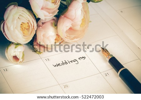 word wedding on calendar with sweet flowers and pen  ,love concept