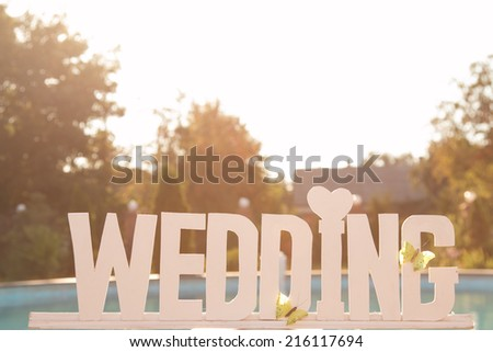 Word wedding, white letters on a board with a pool of blue water. Wedding decor. Caption wedding of wooden letters. Wedding story on holiday and traveling. Celebrating wedding ceremony at the hotel. - stock photo