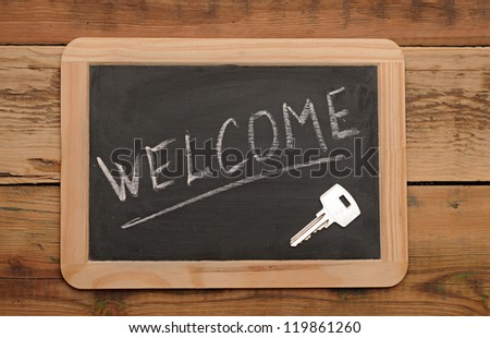 "word ""welcome"" and key on small school wooden blackboard - stock photo"
