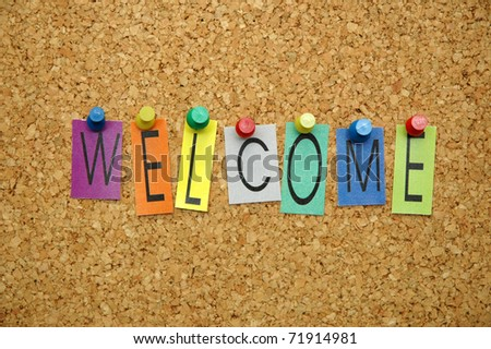 "Word "" welcome  "" placed from colourful small letters on the cork board"