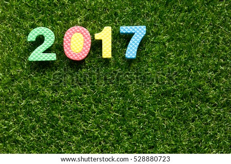 Wording 2017 from toy alphabet on artificial green grass background (Concept of Happy new year)