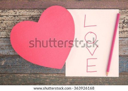 Wording love on Pink Heart gift box and paper and pencil on vintage wood table - stock photo