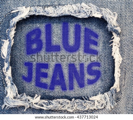 Words Blue Jeans on destroyed torn denim blue jeans patch background, close up - stock photo