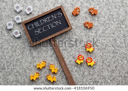 Words CHILDREN'S SECTION word written on small blackboard with cute little animal eraser - stock photo