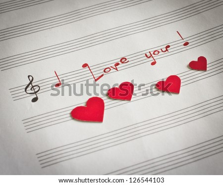 "Words ""I love you !"" in shape of music notes in the music note book with red hearts"